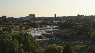 DX0002_176_006 - 5.7K stock footage aerial video ascend and reveal the waterfalls at Falls Park at sunset in Sioux Falls, South Dakota