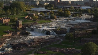 DX0002_176_007 - 5.7K stock footage aerial video descending by the waterfalls at Falls Park at sunset in Sioux Falls, South Dakota