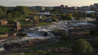 DX0002_176_008 - 5.7K stock footage aerial video of orbiting waterfalls at sunset in Sioux Falls, South Dakota