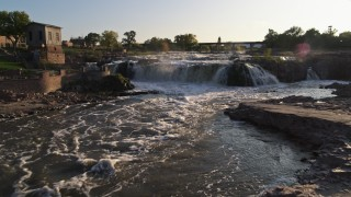 DX0002_176_010 - 5.7K stock footage aerial video of flying low over waterfalls at sunset in Sioux Falls, South Dakota