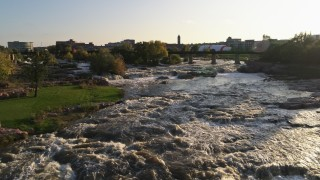 DX0002_176_011 - 5.7K stock footage aerial video of a reverse view of waterfalls at sunset in Sioux Falls, South Dakota