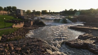 DX0002_176_012 - 5.7K stock footage aerial video of flying by the waterfalls at sunset in Sioux Falls, South Dakota