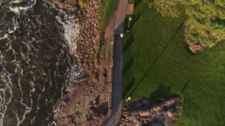 DX0002_176_016 - 5.7K stock footage aerial video a bird's eye view of a path through the park by the river at sunset in Sioux Falls, South Dakota