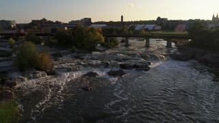DX0002_176_020 - 5.7K stock footage aerial video reverse view of train crossing bridge near waterfalls at sunset in Sioux Falls, South Dakota