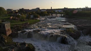 DX0002_176_021 - 5.7K stock footage aerial video reverse view of waterfalls on Big Sioux River at sunset in Sioux Falls, South Dakota
