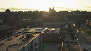 DX0002_176_028 - 5.7K stock footage aerial video orbit county office buildings, cathedral in background at sunset in Downtown Sioux Falls, South Dakota