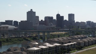 DX0002_177_005 - 5.7K stock footage aerial video ascend from trees for view of the city's skyline and bridge in Downtown Memphis, Tennessee