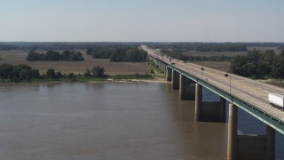 DX0002_177_024 - 5.7K stock footage aerial video following the bridge over the Mississippi River toward Arkansas farmland