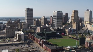 DX0002_179_013 - 5.7K stock footage aerial video descend with view of baseball stadium and high-rise office towers in Downtown Memphis, Tennessee