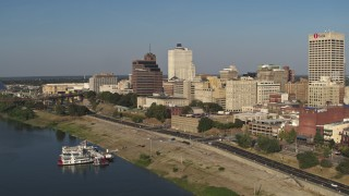 DX0002_180_018 - 5.7K stock footage aerial video reverse view of Raymond James Tower and office buildings near the water, Downtown Memphis, Tennessee