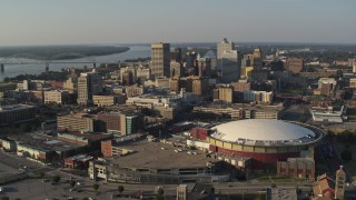 DX0002_180_022 - 5.7K stock footage aerial video of ascend away from FedEx Forum arena and city skyline at sunset, Downtown Memphis, Tennessee