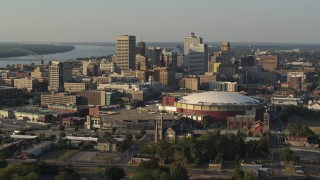 DX0002_180_033 - 5.7K stock footage aerial video flying away from FedEx Forum arena while focused on the skyline at sunset, Downtown Memphis, Tennessee