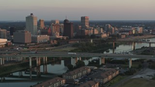 DX0002_181_015 - 5.7K stock footage aerial video a view of the city's skyline behind the bridge and the river at sunset, Downtown Memphis, Tennessee