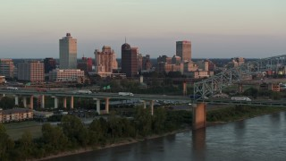 DX0002_181_019 - 5.7K stock footage aerial video focus on the city's skyline behind the bridge at sunset, Downtown Memphis, Tennessee