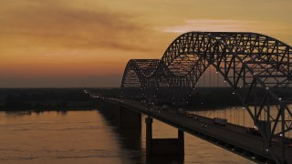 DX0002_181_043 - 5.7K stock footage aerial video flying beside the Hernando de Soto Bridge at sunset, Downtown Memphis, Tennessee