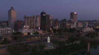 DX0002_182_003 - 5.7K stock footage aerial video of flying by the city's skyline across the river at twilight in Downtown Memphis, Tennessee