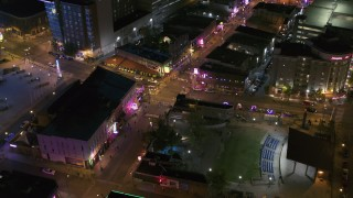DX0002_182_046 - 5.7K stock footage aerial video ascend away from intersection of Beale Street and BB King Boulevard at night in Downtown Memphis, Tennessee