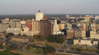 DX0002_186_002 - 5.7K stock footage aerial video orbit and fly away from downtown buildings at sunset, Downtown Memphis, Tennessee