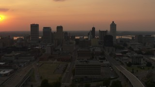DX0002_186_024 - 5.7K stock footage aerial video of the setting sun above the city skyline, Downtown Memphis, Tennessee