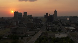 DX0002_186_031 - 5.7K stock footage aerial video fly away from the downtown skyline and the setting sun, then descent, Downtown Memphis, Tennessee