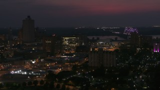 DX0002_187_026 - 5.7K stock footage aerial video city buildings between office tower and bridge at night, Downtown Memphis, Tennessee