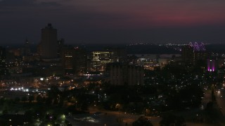 DX0002_187_027 - 5.7K stock footage aerial video orbit city buildings between office tower and bridge at night, Downtown Memphis, Tennessee