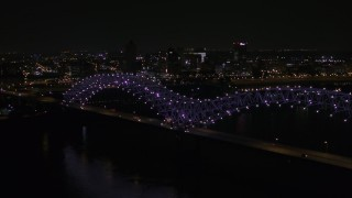 DX0002_187_033 - 5.7K stock footage aerial video a stationary view of the bridge with purple lights and the Downtown Memphis skyline, Tennessee