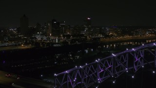 DX0002_187_035 - 5.7K stock footage aerial video of the downtown skyline, reveal the bridge with purple lights at night, Downtown Memphis, Tennessee