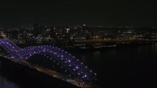 DX0002_187_037 - 5.7K stock footage aerial video ascend past the bridge with purple lights for a view of the skyline at night, Downtown Memphis, Tennessee