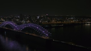 DX0002_187_038 - 5.7K stock footage aerial video flying by the bridge with colorful lights with a view of the skyline at night, Downtown Memphis, Tennessee