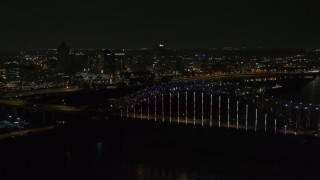 DX0002_187_040 - 5.7K stock footage aerial video of the skyline seen while passing the bridge with colorful lights at night, Downtown Memphis, Tennessee