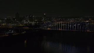 DX0002_187_041 - 5.7K stock footage aerial video of flying away from the skyline and bridge with colorful lights at night, Downtown Memphis, Tennessee