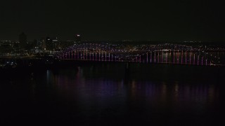 DX0002_187_046 - 5.7K stock footage aerial video a slow approach to the bridge with colorful lights and skyline at night, Downtown Memphis, Tennessee