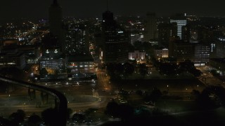 DX0002_187_076 - 5.7K stock footage aerial video fly away from Raymond James Tower and nearby buildings at nighttime, Downtown Memphis, Tennessee