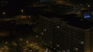 DX0002_188_046 - 5.7K stock footage aerial video ascend by an office building at nighttime, Memphis, Tennessee
