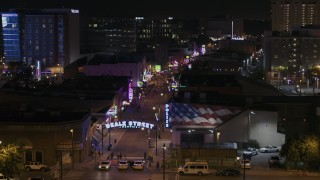 DX0002_188_049 - 5.7K stock footage aerial video descend to reveal the Beale Street sign near clubs and restaurants at nighttime, Downtown Memphis, Tennessee