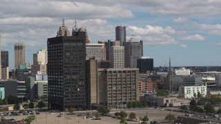 DX0002_189_035 - 5.7K stock footage aerial video descend and flyby office buildings, skyline in the distance, Downtown Detroit, Michigan