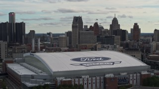 DX0002_191_028 - 5.7K stock footage aerial video focus on downtown skyline and descend by Ford Field, Downtown Detroit, Michigan
