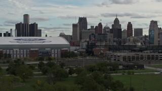 DX0002_191_032 - 5.7K stock footage aerial video descend behind the stadiums with view of the skyline in Downtown Detroit, Michigan