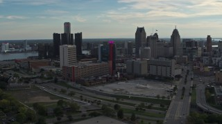 DX0002_192_007 - 5.7K stock footage aerial video a reverse view of tall skyscrapers behind a hotel at sunset, Downtown Detroit, Michigan