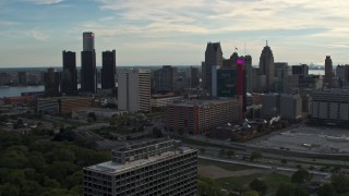 DX0002_192_009 - 5.7K stock footage aerial video slowly passing tall skyscrapers behind a hotel at sunset, Downtown Detroit, Michigan