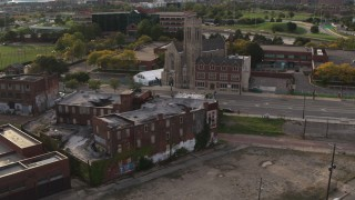 DX0002_192_014 - 5.7K stock footage aerial video orbit an abandoned building and reveal a church at sunset, Detroit, Michigan