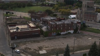 DX0002_192_017 - 5.7K stock footage aerial video circling around an abandoned building at sunset, Detroit, Michigan