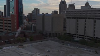 DX0002_192_032 - 5.7K stock footage aerial video ascend while focusing on the Wayne County Jail Division 1 building at sunset, Downtown Detroit, Michigan