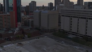 DX0002_192_033 - 5.7K stock footage aerial video descend while focusing on the Wayne County Jail Division 1 building at sunset, Downtown Detroit, Michigan