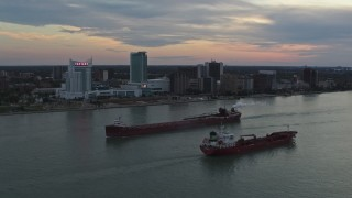 DX0002_192_045 - 5.7K stock footage aerial video of oil tankers passing on the Detroit River near skyline of Windsor, Ontario, Canada, sunset