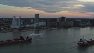 DX0002_192_046 - 5.7K stock footage aerial video of the city skyline and oil tankers on the river, Windsor, Ontario, Canada, sunset