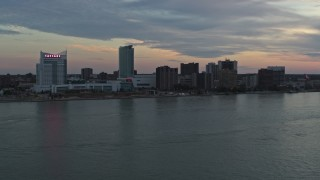 DX0002_192_048 - 5.7K stock footage aerial video ascend from the river for view of skyline, Windsor, Ontario, Canada, sunset