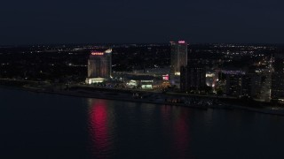 DX0002_193_011 - 5.7K stock footage aerial video of Caesar Windsor hotel and casino across the river at night, Windsor, Ontario, Canada