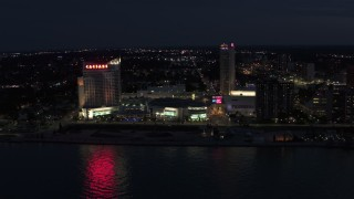 DX0002_193_014 - 5.7K stock footage aerial video stationary view of Caesar Windsor hotel and casino at night, Windsor, Ontario, Canada